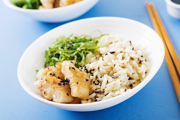Japońskie jedzenie. miska ryżu, gotowanej białej ryby i wakame chuka lub sałatka z wodorostów.