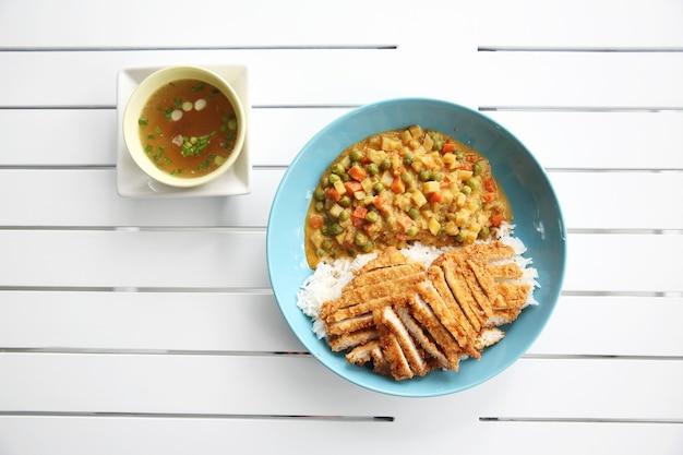 Japońskie jedzenie ryż curry ze smażoną wieprzowiną na drewnianym tle