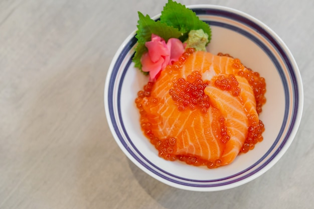 Japońskie jedzenie sashimi z łososia, jajo łososia (ikura), posiekana rzodkiewka i imbir w plasterkach z japońskim donburi z ryżu, don łososia.