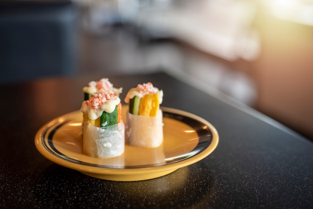 Japońskie jedzenie, stylowe, piękne, z bliska, pyszne na żółtym talerzu i czarnym stole z rozmytym tłem. kopiuj przestrzeń