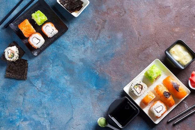 Japońskie jedzenie-sushi, bułki, pałeczki, sos sojowy na tle kamienia, kopia przestrzeń