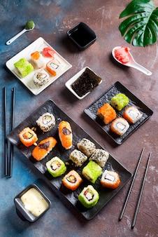 Japońskie jedzenie - sushi, bułki, pałeczki, sos sojowy na tle kamienia