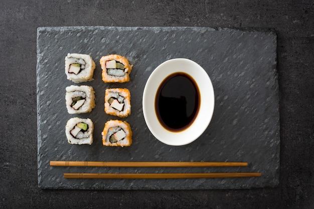 Japońskie jedzenie sushi z sosem sojowym i chopstick na czarny łupek widok z góry