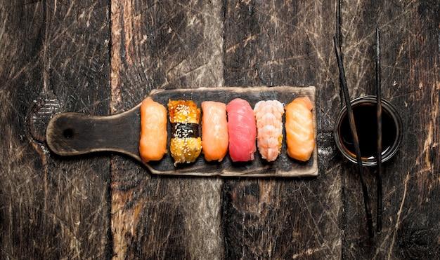 Japońskie jedzenie świeże sushi na starej płycie z sosem sojowym na starym drewnianym tle