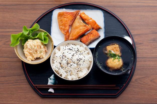 Japońskie jedzenie teriyaki z łososiem z zestawem ryżu z bliska podawane na drewnianym stole.