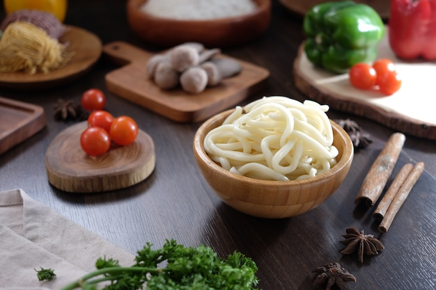Japońskie jedzenie udon na drewnianej misce z pomidorowymi klopsikami papryki wiśni w drewnianym stole