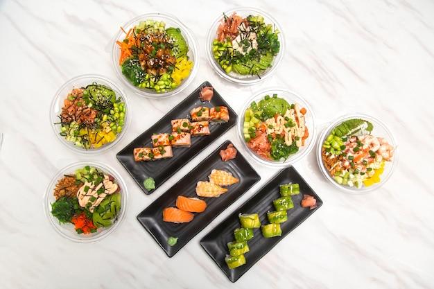Japońskie jedzenie widziane z góry, poke bowl i sushi z awokado i łososia.