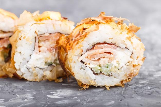 Japońskie mak suszi rolki z tuńczyka ogórkowym serem na czerń betonu tle