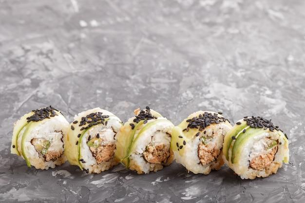 Japońskie maki sushi rolki z tuńczykiem, ogórkiem, czarnym sezamem, serem. widok z boku.