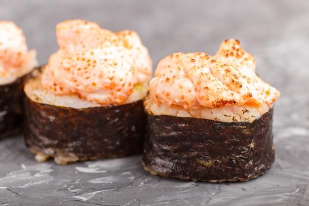 Japońskie maki suszi rolki z latającej ryba ikrą, ser na czerń betonu tle. widok z boku.