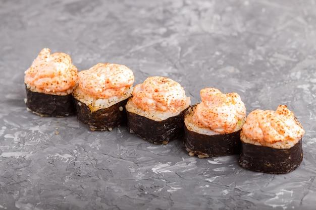 Japońskie maki suszi rolki z latającej ryba ikrą, ser na czerń betonu tle
