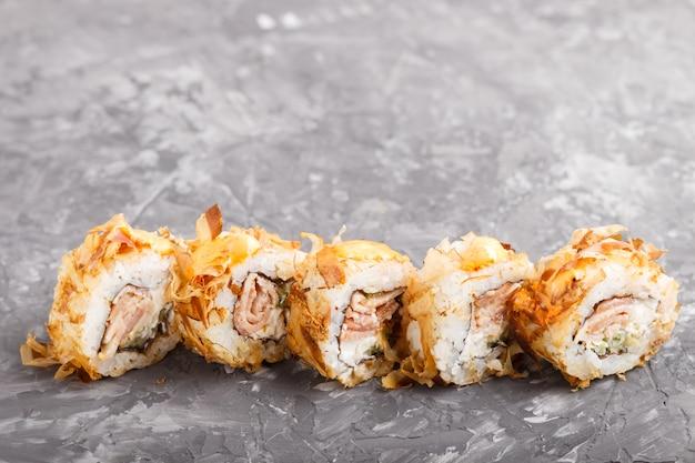 Japońskie maki suszi rolki z tuńczykiem, ogórkiem, serem na czerń betonu tle. widok z boku.
