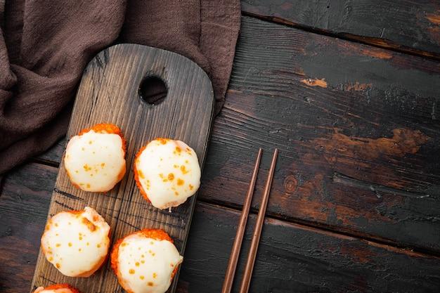 Japońskie roladki sushi o nazwie baked ebi z zestawem wasabi i łososia, na starym ciemnym drewnianym stole