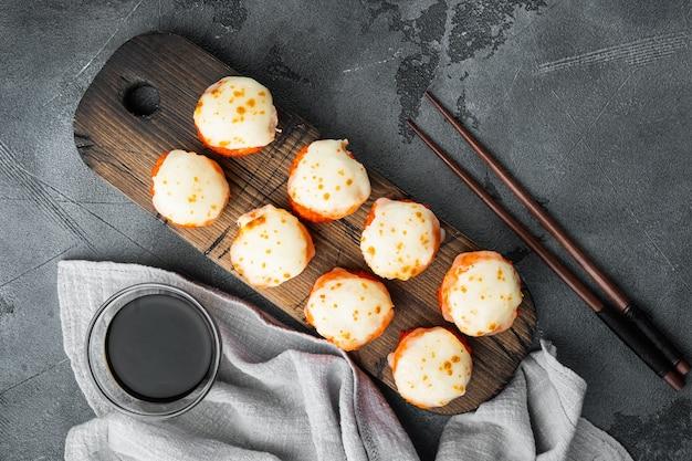 Japońskie roladki sushi o nazwie baked ebi z zestawem wasabi i łososia na szarym kamieniu