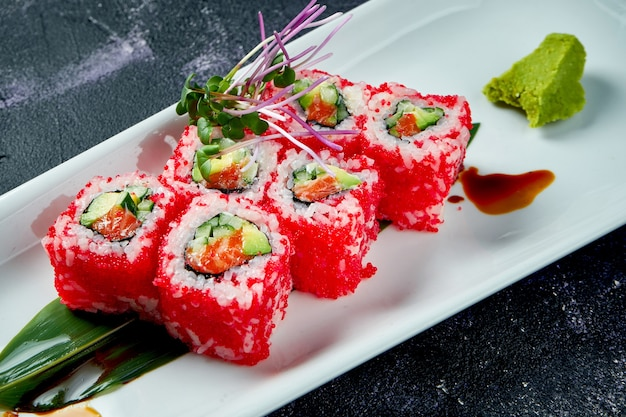 Japońskie roladki sushi z awokado, łososiem i kawiorem tobiko na białym talerzu. roll california. widok z góry