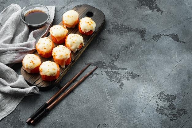 Japońskie rolki sushi o nazwie baked ebi z zestawem wasabi i łososiem, na szarym kamieniu