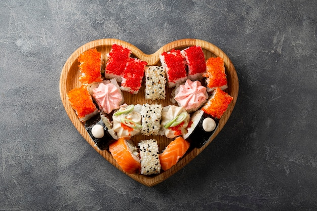 Japońskie rolki w talerzu w kształcie serca na szarym betonowym tle widok z góry