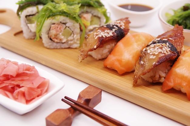 Japońskie sushi na drewnianej tacy podawane z sosem sojowym imbirowym i sałatką z wodorostów