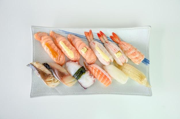 Japońskie sushi nigiri z łososiem, krewetkami, saba, tako, kałamarnicą, engawa na talerzu ceramicznym
