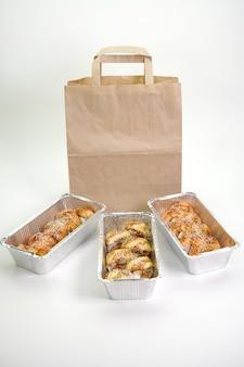Japońskie sushi rolki w foliowych pojemnikach na odosobnionej białej ścianie. pojęcie dostawy