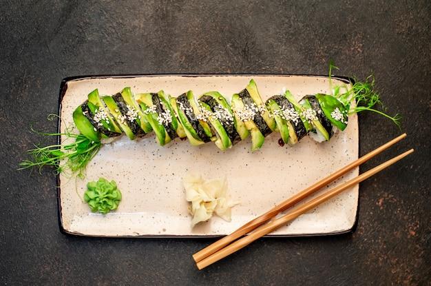 Japońskie sushi rolki zielonego smoka na kamiennym tle gotowe do spożycia