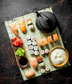 Japońskie sushi z owoców morza na serwetce z gotowanym ryżem i zieloną herbatą. na powierzchni rustykalnej
