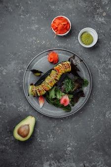 Japońskie sushi - zielony smok. awokado, cebula, łosoś i ser sushi. widok z góry