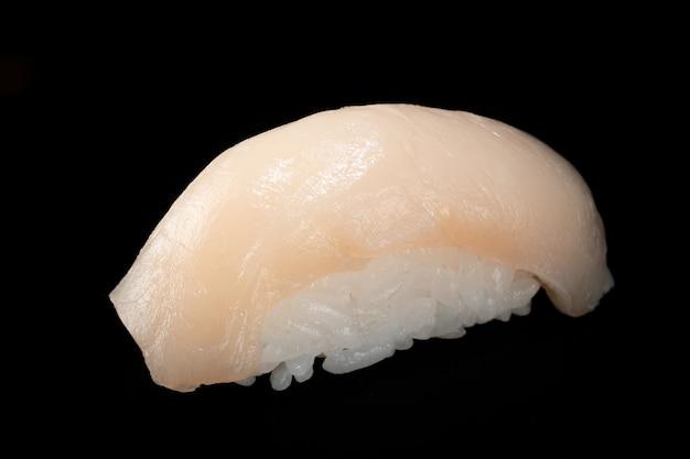 Japońskie świeże sushi nigiri z przegrzebkiem odizolowane na czarno
