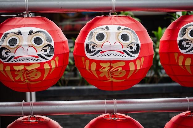 Japońskie szczęśliwe symboliczne lalki wiszące w rzędzie