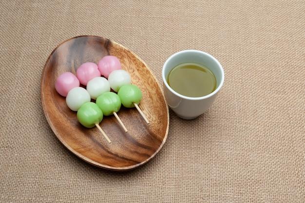 Japońskie tradycyjne słodycze o nazwie dango mochi na drewnianym talerzu z zieloną herbatą.