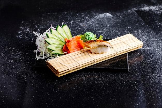 Japońskie unagi na macie do sushi z wasabi, imbirem i ogórkiem.