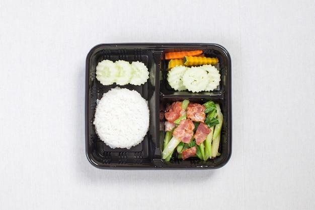 Jarmuż smażony z boczkiem z ryżem wymieszać w czarnym plastikowym pudełku, położyć na białym obrusie, pudełku na jedzenie, tajskim jedzeniu.