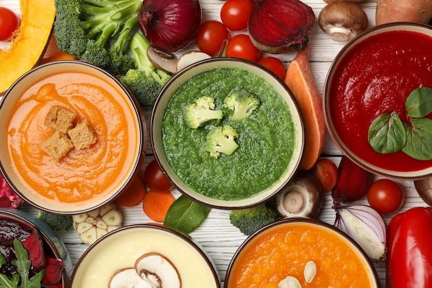 Jarzynowe zupy i składniki na białym drewnianym, odgórnym widoku ,.