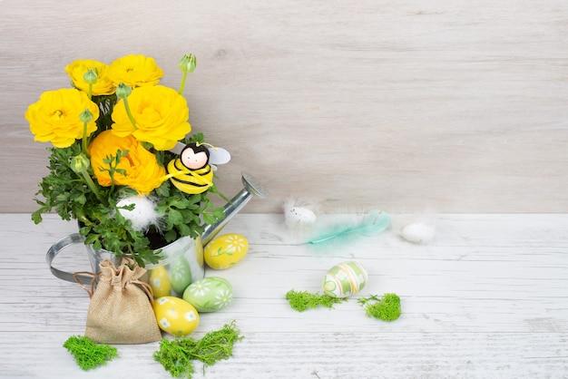 Jaskier jaskier w metalowej konewce, ozdobna pszczoła, pisanki z piórkami, płócienna torba.
