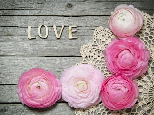 Jaskier kwiaty i tekst kochają na starym szarym drewnianym stołowym odgórnym widoku