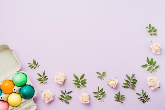 Jaskrawa kolekcja barwioni jajka w pojemniku blisko kwitnie i roślina