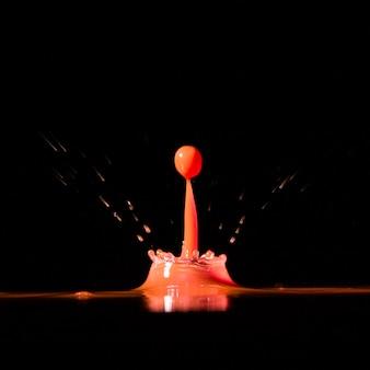 Jaskrawa kropelka spada w wodzie na czerni