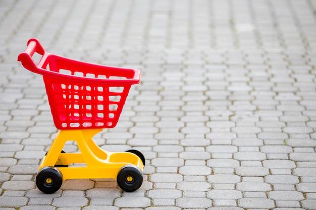 Jaskrawa plastikowa kolorowa wózek na zakupy zabawka outdoors na pogodnym letnim dniu