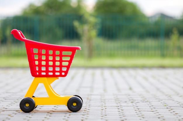 Jaskrawa plastikowa kolorowa wózek na zakupy zabawka outdoors na pogodnym letnim dniu.