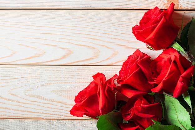 Jaskrawe czerwone róże z zielonymi liśćmi kłamają na lekkim naturalnym drewnianym tle z copyspace