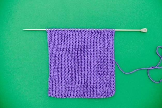 Jaskrawe purpury dziający szalik z dziewiarską igłą na zielonym tle.