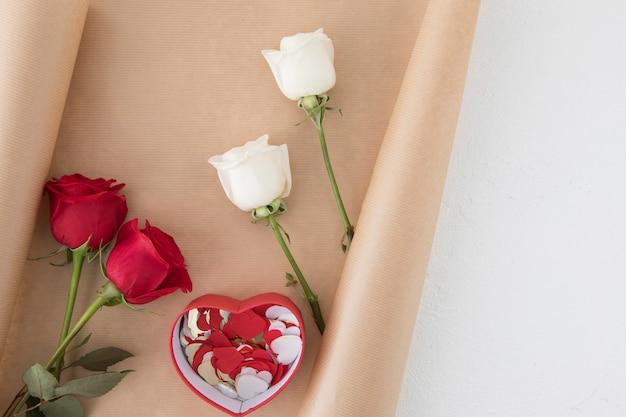 Jaskrawe róże z papierowymi sercami w pudełku