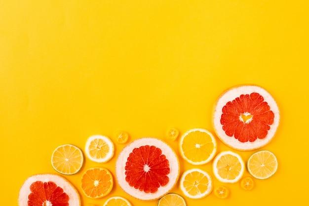 Jaskrawe stubarwne cytrus owoc na żółtym tle, lata mieszkania nieatutowy pojęcie.
