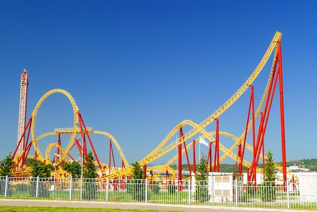 Jaskrawoczerwone i żółte konstrukcje kolejek górskich w miejskim parku rozrywki