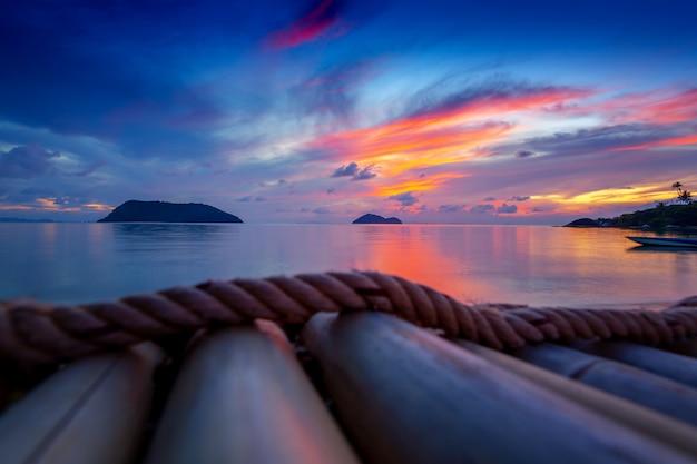 Jaskrawy kolorowy zmierzch na tropikalnej wyspie z sylwetkami drzewka palmowe i tapetą, pocztówka, koh phangan wyspa tajlandia