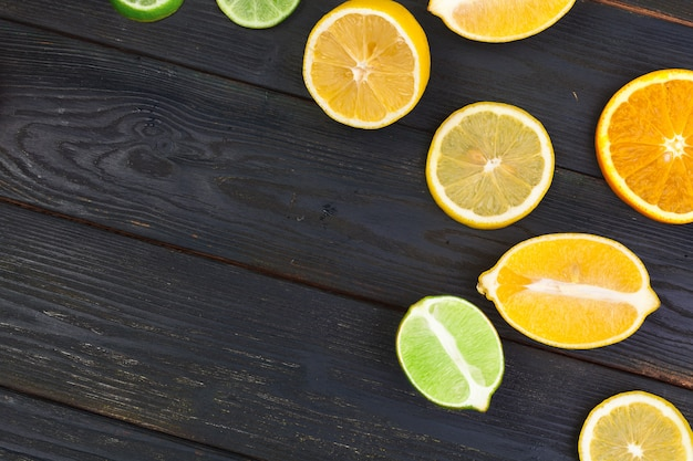 Jaskrawy skład cytrus owoc na czarnym drewnianym tle