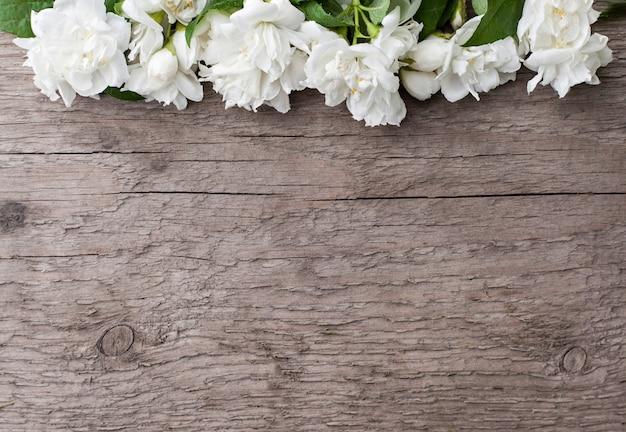 Jaśmin kwitnie na drewnianym stole. miejsce na twój tekst. skopiuj miejsce