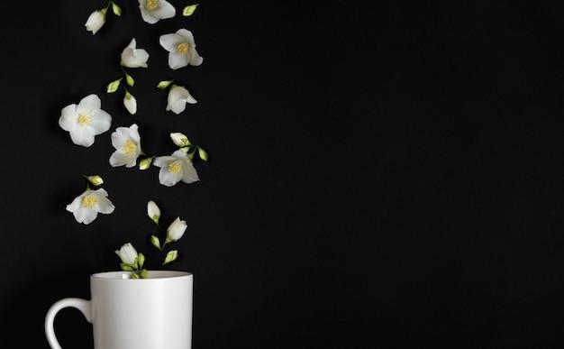 Jaśminowe kwiaty wlatują do białej filiżanki na czarnym tle jaśminowa herbata w filiżance