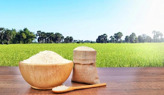 Jaśminowy rice w drewnianym pucharze i parcianym burlap na drewnianym biurko stole.
