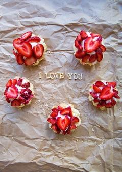 Jasna babeczka z truskawkami leży na papierze rzemieślniczym, napis kocham cię